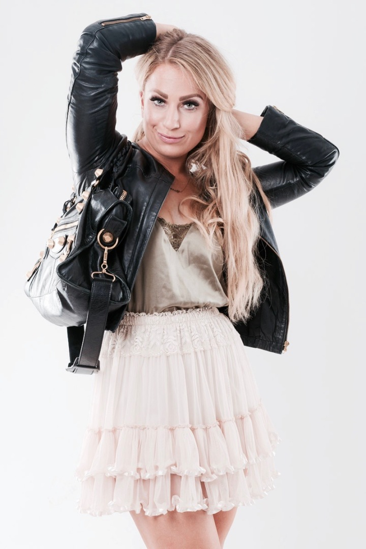 woman in black leather jacket, eyes closed, view to the buttom, blond hair and make up, silktop and Carrie necklace. Balenciaga Giant bag, cream skirt, ruffles, black shoes and long blond hair